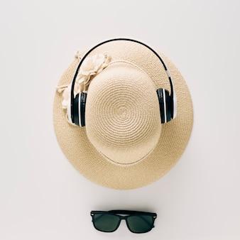 Draufsicht strohhüte mit gläsern und musikkopfhörern
