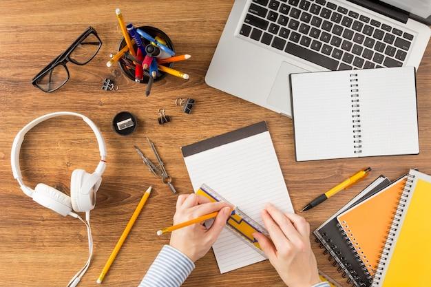 Draufsicht-student, der geometrieprobleme auf notizblock tut