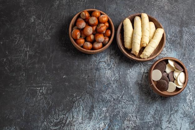 Draufsicht süße bagels mit keksen und nüssen auf der dunklen oberfläche
