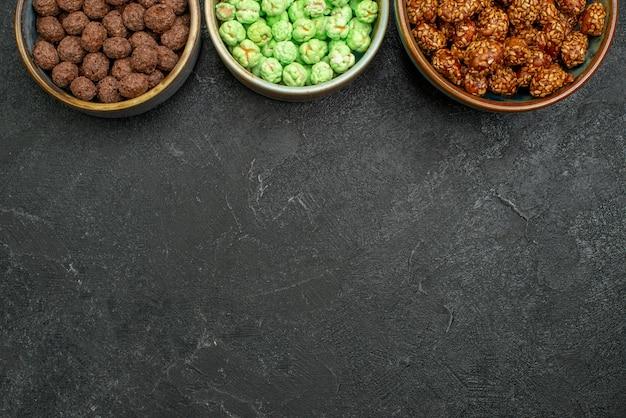 Draufsicht süße bonbons in töpfen auf grauem hintergrund zuckersüßigkeit goodie sweet