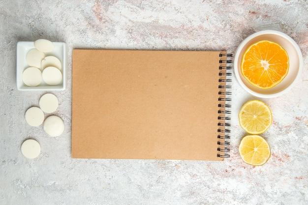 Draufsicht süße bonbons mit notizblock auf weißem tischbonbonkeksplätzchen