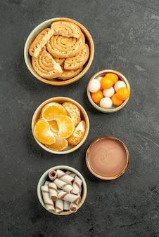 Draufsicht süße kekse mit bonbons auf dunkelgrauem hintergrund