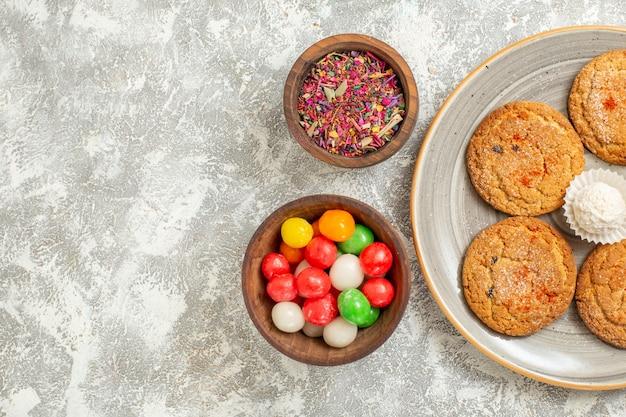 Draufsicht süße kekse mit bonbons auf weißem hintergrund