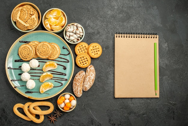 Draufsicht süße kekse mit bonbons und keksen auf grauem hintergrund