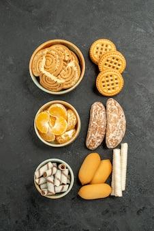 Draufsicht süße kekse mit früchten und bonbons auf dem dunklen hintergrund