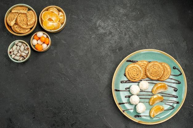 Draufsicht süße kekse mit kokosnussbonbons und früchten auf dunkelgrauem schreibtisch
