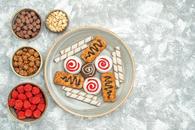 Draufsicht süße kekse mit kuchen und süßigkeiten auf weißem hintergrundzuckerkeks süßer kuchenplätzchen
