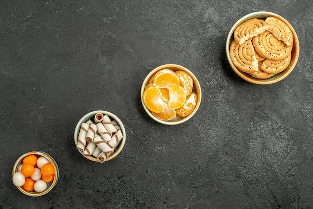 Draufsicht süße kekse mit mandarinen auf dunklem hintergrund