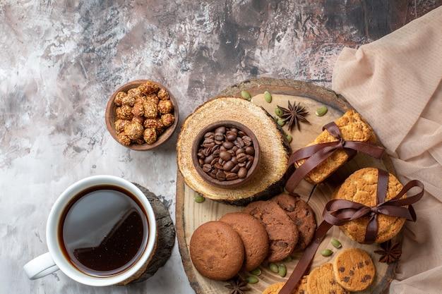 Draufsicht süße kekse mit nüssen und tasse kaffee auf dem leuchttisch
