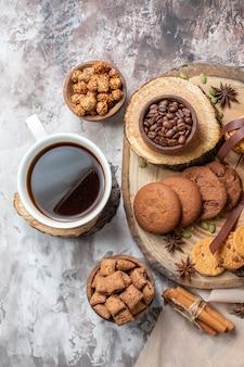 Draufsicht süße kekse mit nüssen und tasse kaffee auf hellem schreibtisch