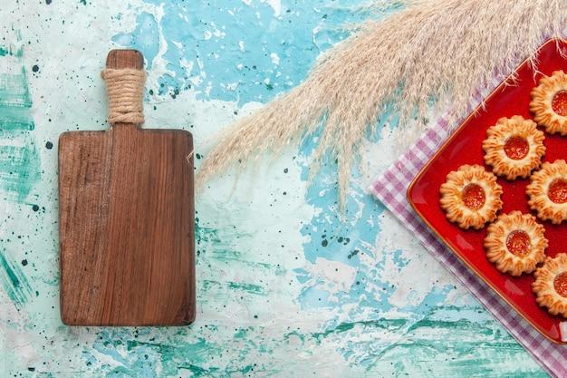 Draufsicht süße kekse mit orange marmelade auf dem hellblauen hintergrund