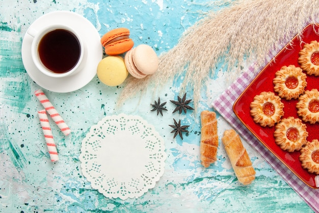 Draufsicht süße kekse mit orange marmelade bagels und tasse tee auf dem blauen hintergrund