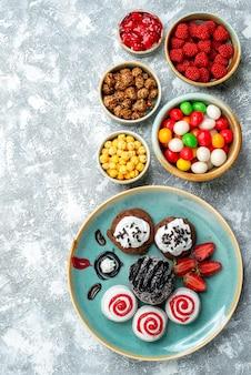 Draufsicht süße kekse mit schokoladenkuchen und bonbons auf hellweißem hintergrund bonbonzucker-kekskuchen süßer tee