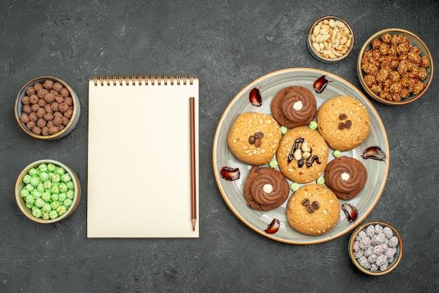 Draufsicht süße kekse mit süßigkeiten auf dunkelgrauem bodenzuckerplätzchen süßer kekskuchen-tee
