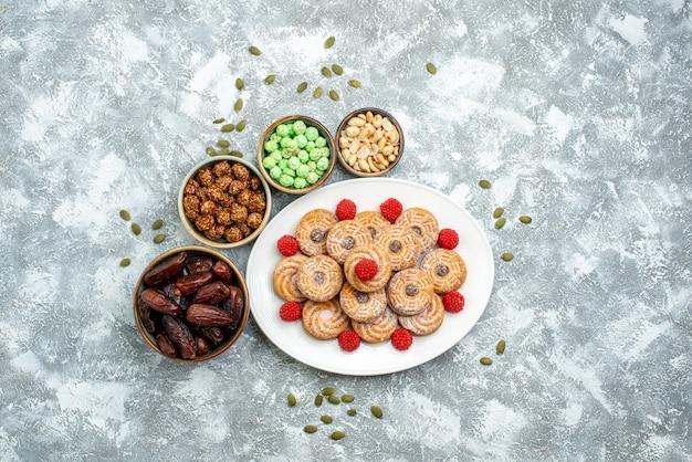 Draufsicht süße kekse mit süßigkeiten und konfekt auf weißem hintergrund kekse zuckerkeks tee süßer kuchen