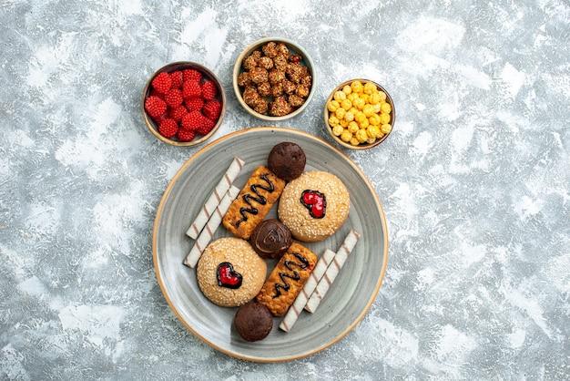 Draufsicht süße kekse mit zuckersüßigkeiten auf hellweißem hintergrundplätzchenkekszuckerkuchen süßer tortenkuchen
