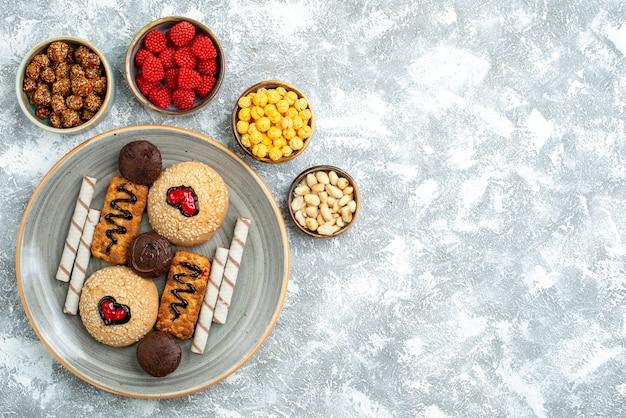 Draufsicht süße kekse mit zuckersüßigkeiten auf weißem hintergrundplätzchenkekszuckerkuchen süßer tortenkuchen