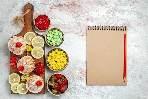 Draufsicht süße kleine kuchen mit zitronenscheiben und bonbons auf weißem hintergrund zitrusfruchtfrucht süßer kekskuchen