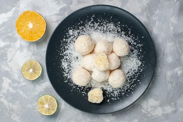 Draufsicht süße kokosnussbonbons innerhalb platte auf weiß