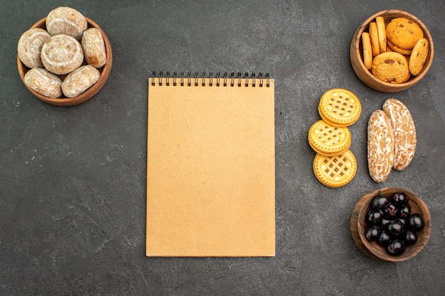 Draufsicht süße kuchen mit keksen und oliven auf einem süßen kuchenkuchen der dunklen oberfläche
