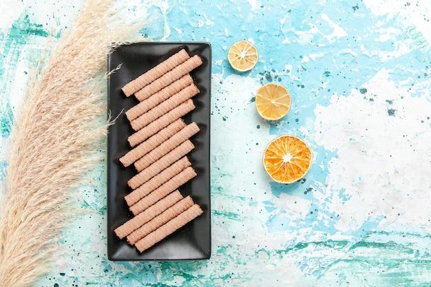 Draufsicht süße lange kekse innerhalb der schwarzen kuchenform auf dem blauen hintergrund