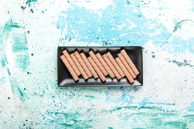 Draufsicht süße lange kekse innerhalb der schwarzen kuchenform auf dem hellblauen hintergrund