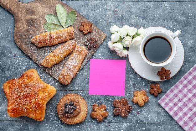 Draufsicht süße leckere kekse mit tasse kaffee und süßem armreifgebäck der graue hintergrundplätzchenzuckersüßkaffee