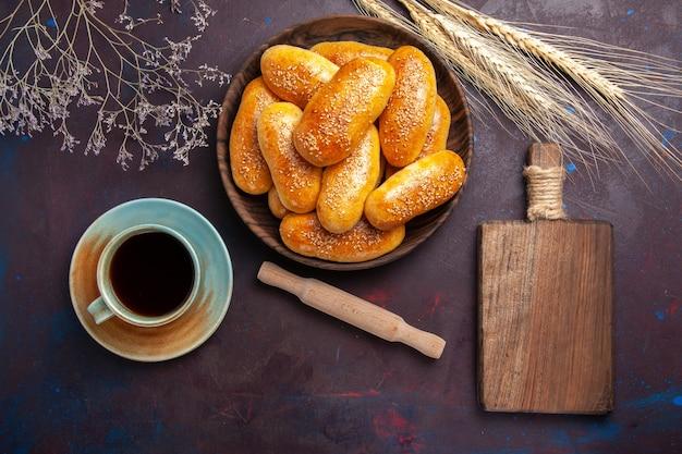 Draufsicht süße pastetchen mit tasse tee auf dem dunklen hintergrund gebäck teig mahlzeit essen pastetchen tee