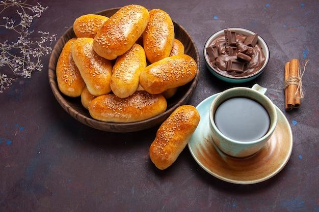 Draufsicht süße pastetchen mit tasse tee und schokolade auf dunklem hintergrund gebäck teig mahlzeit essen pastetchen tee