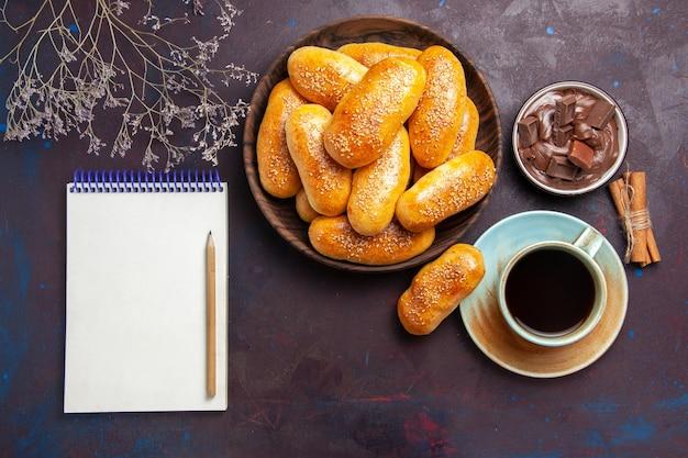 Draufsicht süße pastetchen mit tasse tee und schokolade auf dunklem schreibtisch gebäck teig mahlzeit essen pastetchen tee
