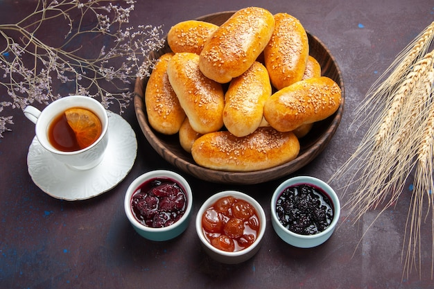 Draufsicht süße pastetchen mit tee und marmelade auf dunklem hintergrund teemehl gebäck pastetchen teig essen