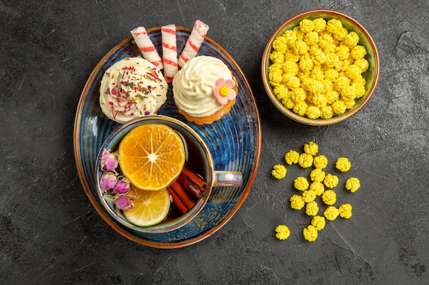 Draufsicht süßigkeiten auf dem teller cupcakes mit weißer sahne auf der untertasse eine tasse tee mit zitrone und zimtstangen schüssel mit gelben süßigkeiten auf dem tisch