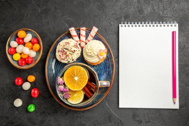 Draufsicht süßigkeiten auf dem teller der appetitlichen cupcakes schalen mit bunten süßigkeiten neben dem weißen notizbuch und rosa bleistift auf dem tisch