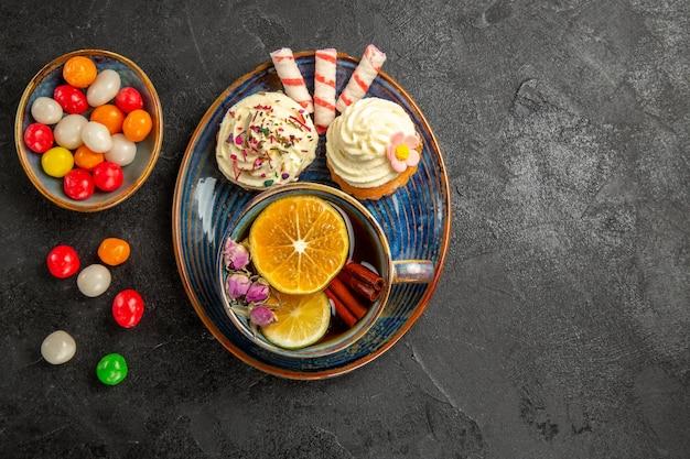 Draufsicht süßigkeiten auf dem teller zwei appetitliche cupcakes und süßigkeiten auf der untertasse eine tasse tee mit zitronen- und zimtstangen schüsseln mit bunten süßigkeiten auf dem tisch