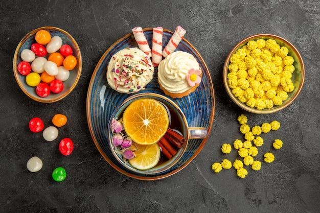 Draufsicht süßigkeiten auf dem teller zwei cupcakes mit sahne auf der blauen untertasse eine tasse tee mit zitrone und zimtstangen schüsseln mit bunten süßigkeiten auf dem tisch
