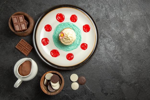 Draufsicht süßigkeiten auf dem tisch ein appetitlicher cupcake mit saucen neben den schalen mit schokolade und schokoladencreme auf dem schwarzen tisch