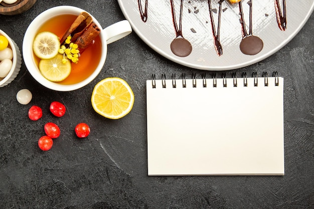 Draufsicht süßigkeiten und tee weiße tasse tee mit zimtstangen und zitrone neben dem weißen notizbuch der teller mit kuchen und schalen mit schokolade und süßigkeiten auf dem dunklen tisch
