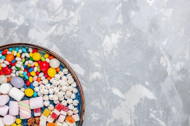 Draufsicht-süßigkeitszusammensetzung verschiedenfarbige bonbons mit marshmallow auf weißer wandzuckerbonbonbonbon-süßwaren