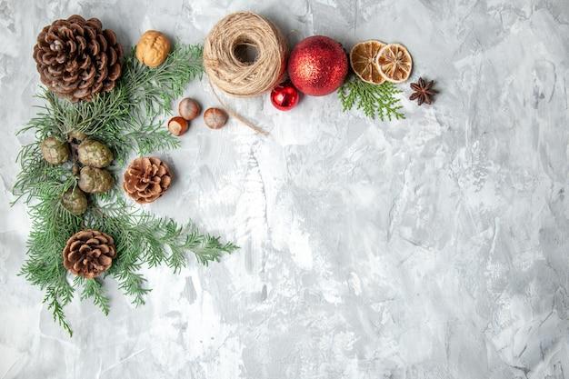 Draufsicht tannenbaum zweige kegel weihnachtsspielzeug auf grauem hintergrund