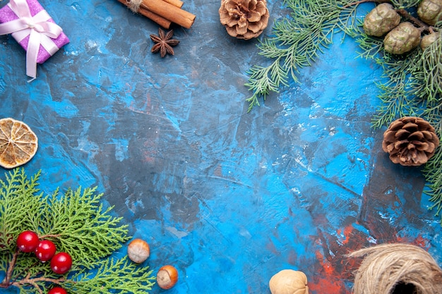 Draufsicht tannenzweige tannenzweige kegel weihnachtsbaum spielzeug auf blauem hintergrund