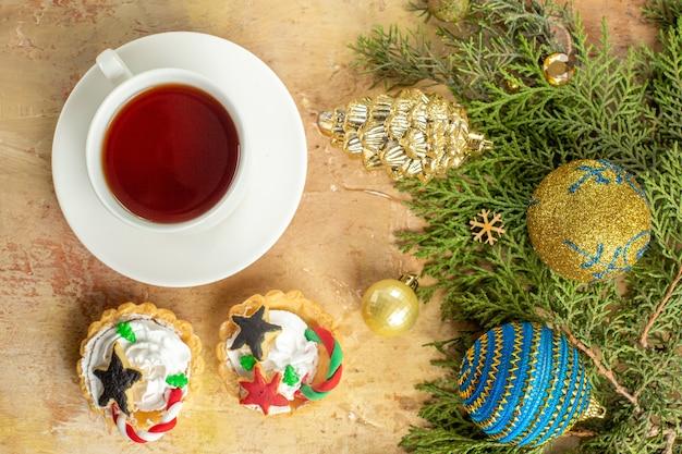 Draufsicht tannenzweige weihnachtsbaum ornamente cupcakes eine tasse tee auf beigem hintergrund