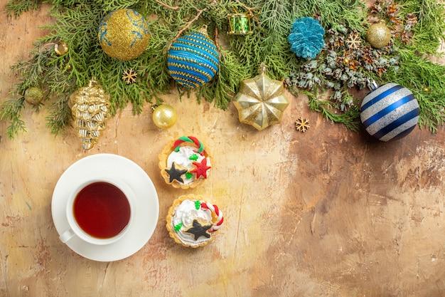 Draufsicht tannenzweige weihnachtsbaum ornamente eine tasse tee cupcakes auf beigem hintergrund