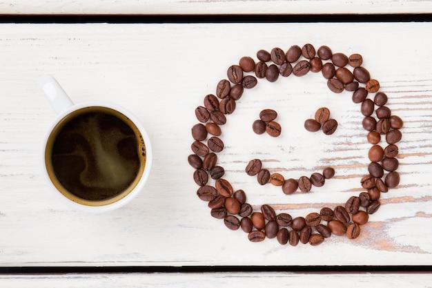 Draufsicht tasse heißen kaffee und bohnen in form eines smileys. weiße holzbretter auf der oberfläche.