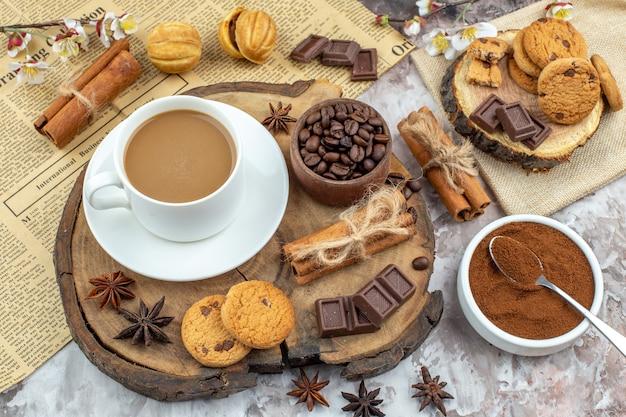 Draufsicht tasse kaffee kekse schüssel mit gerösteten kaffeebohnen schokolade zimtstangen anis auf holzbrett kakaoschale