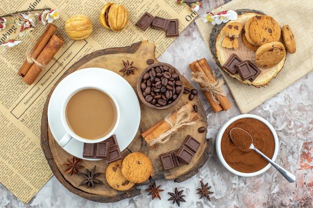 Draufsicht tasse kaffee kekse schüssel mit gerösteten kaffeebohnen schokolade zimtstangen anis sterne auf holzbrett kakaoschale zeitung auf tisch