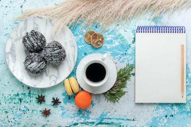Draufsicht tasse kaffee mit französischen macarons und schokoladenkuchen auf hellblauem hintergrundkuchen backen keks süße schokoladenzuckerfarbe