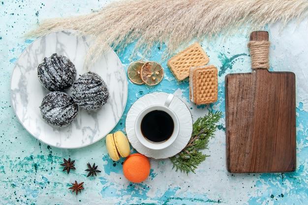 Draufsicht tasse kaffee mit französischen macarons waffeln und schokoladenkuchen auf blauem hintergrundkuchen backen keks süße schokoladenfarbe zucker