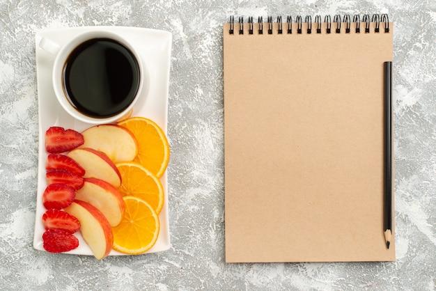 Draufsicht tasse kaffee mit geschnittenen äpfeln orangen und erdbeeren auf weißen hintergrundfrüchten reifen frischen milden