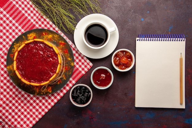 Draufsicht tasse kaffee mit köstlichem dessertkuchen und fruchtmarmeladen auf dunklem schreibtisch süßer fruchtkekskeks süß