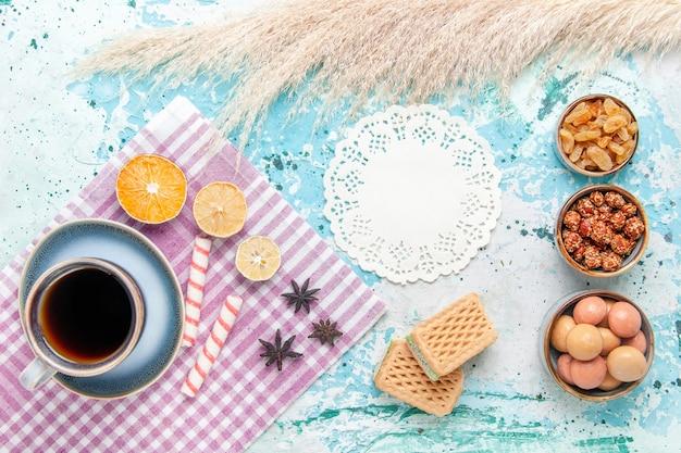 Draufsicht tasse kaffee mit rosinenwaffeln und konfekt auf dem hellblauen hintergrundkuchen backen süßen zuckerkuchenplätzchen